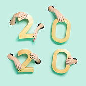 Female hands hold golden new year 2020 digits through a hole on neon mint background. Minimalistic creative xmas isolated concept.