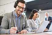 Smiling friendly male customer support agent wearing headset taking some notes while talking to a client in call center