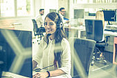 Smiling young business woman with headset working in call center