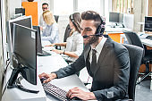 Handsome young customer support agent with headset working on computer in call center.
