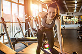 Sportswoman lifting dumbbells on exercise bench at gym