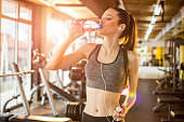Fit slim sportswoman drinking water during sports training at gym