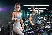 Beautiful sporty young woman and handsome man showing thumbs up while sitting on indoors cycling bikes in the gym