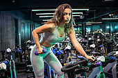 Young woman holding weight and working out on the exercise bike at the gym