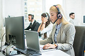 Beautiful young female customer support operator with headset working on laptop in call centre