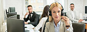 Portrait of beautiful female customer support operator with headset in call center