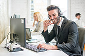 Smiling customer support phone operator talking with a client in call centre