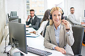 Portrait of smiling female customer service representative with colleagues working in office