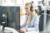 Friendly smiling customer support agent woman talking with client using headset and typing on computer in call center.