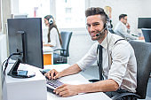 Handsome young customer support operator with hands-free headset working using computer in call center.