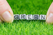 Word GREEN written in metal letters laid on grass and held between the fingers of a woman. Concept of ecology background