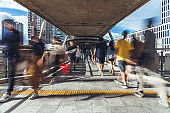 Motion blur of crowded Asian people walking on elevated public walkway. Commuter lifestyle, Asia city life, or pedestrian transportation concept