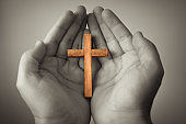 Person holding wooden cross in palm of hands.