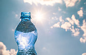 Bottle of water against a sunny sky background.