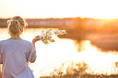 Back view on young woman by the lake on the sunset. Girl with apple trees flowers enjoying summer sunset in the park. Happy woman with bouquet, outdoors. Lifestyle and happiness concept