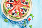 Top view of watermelon pizza with berries, cream and mint