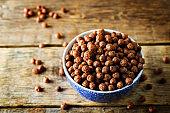 Breakfast crunchy chocolate balls on a dark wood background