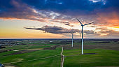 Aerial view of wind turbines and green felds at sunset