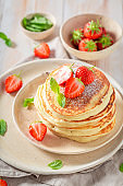 Homemade american pancakes with powdered sugar and sweet strawberries
