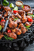 Closeu of spicy grilled chicken leg on metal grate