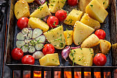 Tasty baked potatoes na grill with tomatoes, garlic and rosemary