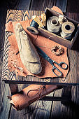 Top view of cobbler workshop with tools, shoes and leather