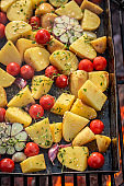 Tasty baked potatoes na grill with garlic, rosemary and oil