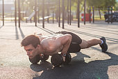 Muscular male athlete doing push ups exercises