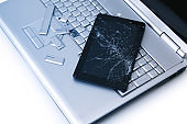A silver laptop with a broken keyboard, tablet with a cracked display. A close-up picture of part of broken laptop and cracked screen on a tablet.