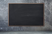 Blackboard texture. Empty blank black chalkboard with chalk traces Concrete wall, cement background.