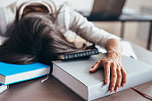 Tired woman sleeping on table face and hands on books