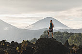 Young man standing on top of stone and enjoying amazing volcanic mountain Agung view in Bali. Travel and active lifestyle concept.