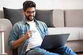 Hipster sitting on floor in living room and using credit card.