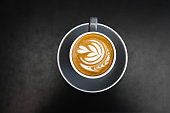 Gray cup of fresh cappuccino with latte art on dark black metal table background. Empty place for text, copy space. Coffee addiction concept. Top view from above.
