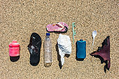Various types of plastic waste collected on the beach on sand background