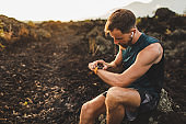 Runner checking training results on smart watch. Male athlete using fitness tracker.
