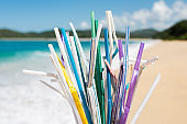 Heap of used plastic straws on background of clean tropical beach and ocean waves