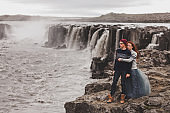 Happy hipster couple in love walking near popular Selfoss waterfall in Iceland. Traditional wool sweaters, red hair, gray skirt. Dramatic nordic landscape, cold weather.