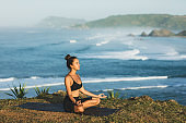Woman practicing yoga and sitting in lotus pose outdoor with amazing ocean view. Health and well-being concept. nature background.