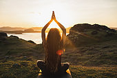 Young woman practicing yoga outdoors.  Spiritual harmony, introspection and well-being concept. Landscape background
