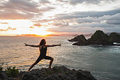 Young slim woman practicing yoga at sunset with beautiful ocean and mountain view. Workout outdoors, sport and well-being concept. Colorful and majestic sunset.