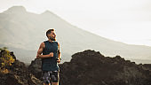 Young athlete man trail running in mountains in the morning. Healthy lifestyle concept. Panoramic photo with empty copy space.