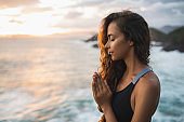 Young woman praying and meditating alone at sunset with beautiful ocean and mountain view. Self-analysis and soul-searching. Spiritual and emotional concept. Introspection, introversion and soul healing.