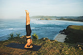 Woman practicing yoga and making handstand pose outdoor with amazing ocean view. Health and fitness concept. Nature background.