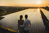 Blurred couple in love watching sunrise on famous Bali landmark Jatiluwih rice terraces. Beautiful morning view with warm orange sun light. Wanderlust and travel concept.