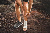 Male runner holding injured leg close-up and suffering with pain. Leg injury. Sprain ligament or tendon while running outdoors. Compression bandage on ankle.