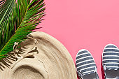 Summer fashion tropical concept. Women's female beachwear straw hat canvas striped shoes coconut green palm leaf on pink background. Vacation relaxation luxury. Creative pop art flat lay