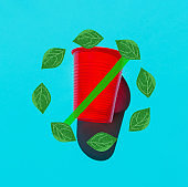 Red plastic drinking cup with no symbol banned sign from hand drawn green leaves circle on blue backdrop. Environmental protection plastic-free zero waste ocean pollution concept. Creative poster