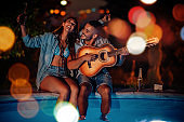 Couple enjoying in music near swimming pool