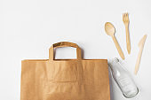 Brown Kraft paper grocery shopping bag wooden flatware cutlery on white background. Plastic-free alternatives zero waste environmental protection nature friendly living. Mock up with copy space
